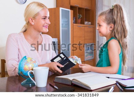 Allowance of pocket money: cute little girl and mother with purse