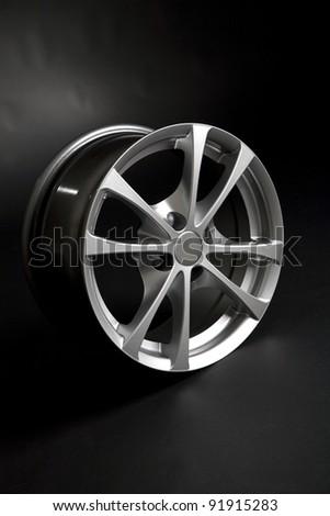 Alloy rim on black background - stock photo