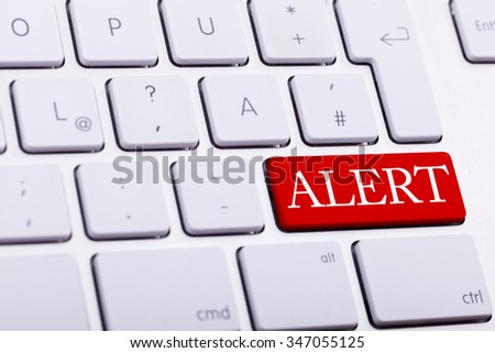 Alluminium keyboard with alert word written on red button close up photo