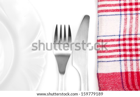 Alluminum silverware next to a plate and kitchen towel