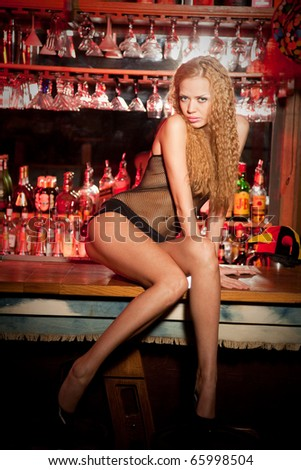 Alluring and fashion girl sitting on the bar table;