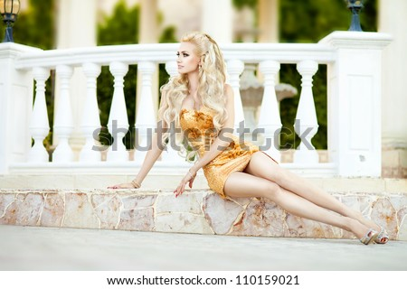alluring blond relaxing in luxury hotel. Stylish rich slim girl in sexy golden dress with healthy glossy curly hair at villa. Fashion glamorous shot at vacation resort spring-summer. Series - stock photo
