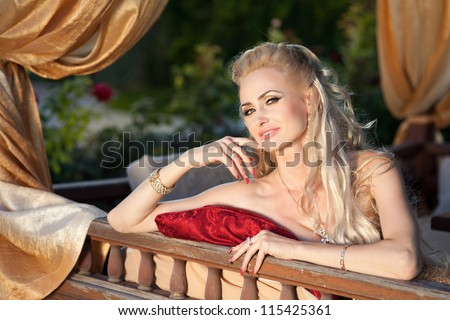 alluring blond relaxing in luxury interior. Stylish rich slim girl in sexy golden dress with healthy glossy curly hair at hotel villa apartment. Fashion glamorous shot at vacation resort autumn - stock photo