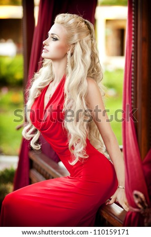 alluring blond relaxing in luxury interior. Stylish rich slim girl in sexy red dress with healthy glossy curly hair at hotel villa apartment. Fashion glamorous shot at vacation resort summer. Series - stock photo