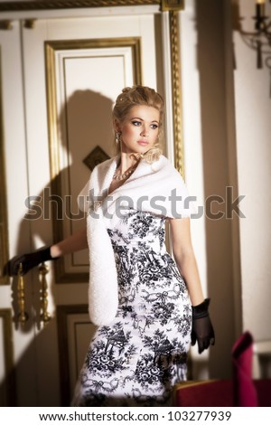 alluring blond rich woman in luxury hotel. Stylish slim girl in gloves  elegant dress and fur with healthy glossy hair at villa apartment leaves a room. Fashion glamorous model in jewellery - stock photo