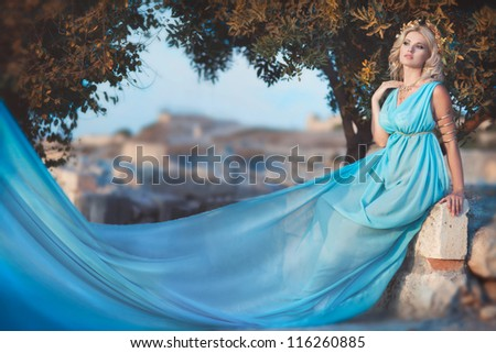 alluring blond woman outdoor in Greek goddess style with golden jewelery in luxury dress on sunset near ancient ruins. stylish romantic girl in blue silk. romantic concept. Amazing Nymph. Greece - stock photo