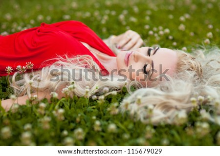 Alluring blonde woman posing in autumn park. Stylish rich slim girl in sexy red dress with healthy glossy curly hair at green grass. Beautiful lady relaxing on nature. - stock photo