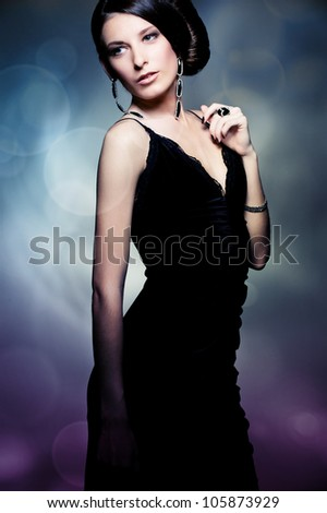 alluring sexy woman in evening black dress posing over dark background - stock photo