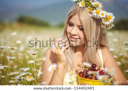 alluring sexy woman relaxing and posingin the field with fresh strawberry. Beautiful happy blonde girl enjoying hot summer sun. Romantic slim lady at vacation.