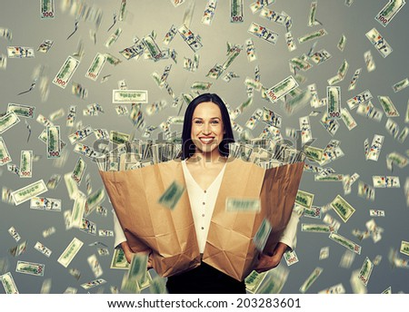 alluring smiley businesswoman holding two paper bags with money under dollar's rain - stock photo