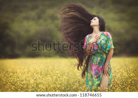 Alluring woman at blossom field with extra long hair on wind. Beautiful  girl in colorful dress posing outdoor. Sexy young lady on nature enjoying freedom. Happy  woman outdoors in autumn park - stock photo