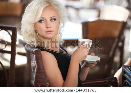 Alluring woman drinking coffee in cafe restaurant in morning sexy blonde girl with cup of latte cappuccino happy smiling. Beautiful retro woman in cafe with mug of hot chocolate. Glamour vintage woman - stock photo
