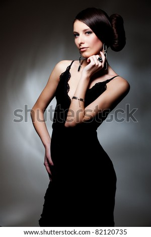 alluring woman in black dress posing over dark background - stock photo