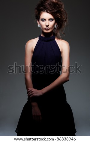 alluring woman in evening dress posing over dark background - stock photo