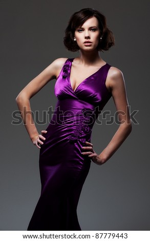 alluring woman in evening violet dress posing over dark background