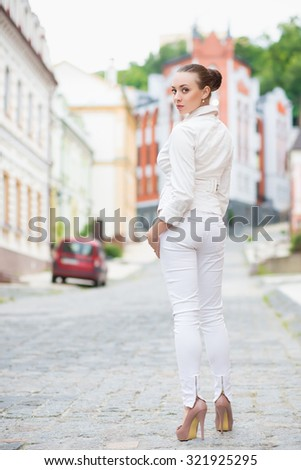 Alluring young brunette in white pants and jacket posing outdoors - stock photo