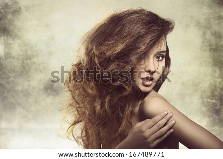 alluring young girl posing in fashion shoot with naked shoulder and creative bushy hairdo  - stock photo