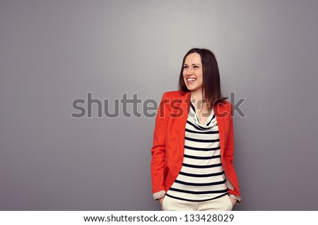 alluring young woman looking up and laughing. studio shot over dark background - stock photo