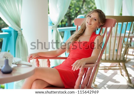 alluring young woman sitting on the chair and looking at camera. shot in the cafe - stock photo
