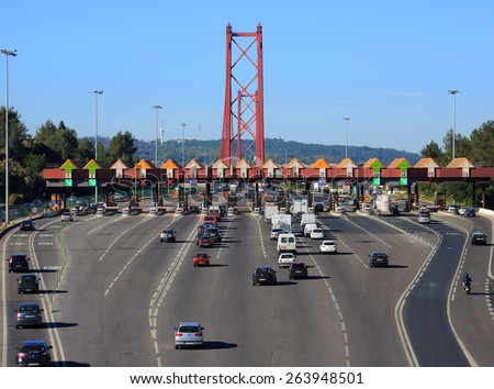 """ALMADA, PORTUGAL - MARCH 06: Toll booths and motorway approach to the 25th Of April Bridge """"Ponte 25 Abril"""" which spans from Almada to Lisbon on the Tagus River. On March 06, 2015 in Almada, Portugal. - stock photo"""