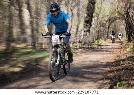 "ALMATY, KAZAKHSTAN - APRIL 19, 2014: I. Genin (N30) in action at cross-country competition ""Open season - Bikes relay 2014""  - stock photo"