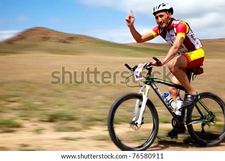 "ALMATY, KAZAKHSTAN - APRIL 30: J.Satkynaliev (N1) in action at Adventure mountain bike cross-country marathon in mountains ""Jeyran Trophy 2011"" April 30, 2011 in Almaty, Kazakhstan. - stock photo"