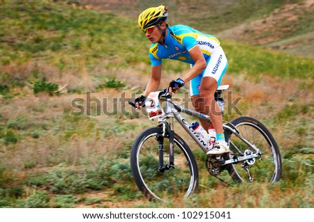 """ALMATY, KAZAKHSTAN - APRIL 29: K.Kazantcev (N2) in action at Adventure mountain bike cross-country marathon in mountains """"Jeyran Trophy 2012"""" April 29, 2012 in Almaty, Kazakhstan. - stock photo"""