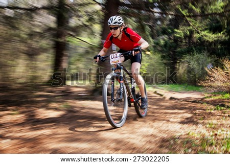 "ALMATY, KAZAKHSTAN - APRIL 19, 2015: M.Getmanchuk (N1) in action at cross-country competition ""Open season - Bikes relay 2015""  - stock photo"