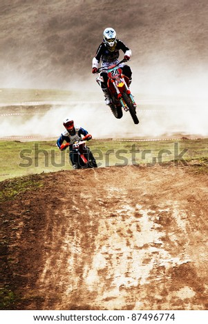 "ALMATY, KAZAKHSTAN - APRIL 10: V.Brikun(24) flies through the air at the Motocross competition ""Fabrichny Cup""- Open Championship of Kazakhstan on April 10, 2011 in Kargaly, Kazakhstan. - stock photo"