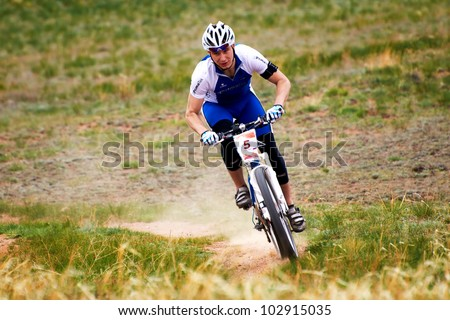 "ALMATY, KAZAKHSTAN - APRIL 29: V.Moga (N5) in action at Adventure mountain bike cross-country marathon in mountains ""Jeyran Trophy 2012"" April 29, 2012 in Almaty, Kazakhstan. - stock photo"