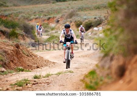 "ALMATY, KAZAKHSTAN - APRIL 29: V.Zasypkin (N23) in action at Adventure mountain bike cross-country marathon in mountains ""Jeyran Trophy 2012"" April 29, 2012 in Almaty, Kazakhstan. - stock photo"