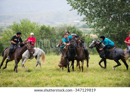 "ALMATY, KAZAKHSTAN - JULY 26 : A traditional nomad game of ""Kokpar"" in action on July 26, 2015 in Almaty, Kazakhstan. Kokpar is played on horseback to carry dead goat carcass into a goal."