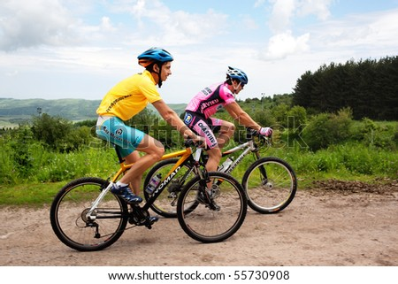 "ALMATY, KAZAKHSTAN - JUNE 20: M.Dzolba (left) and I.Popov in action at Adventure mountain bike cross-country competition ""Ak Bulak 2010"" June 20, 2010 in Almaty, Kazakhstan - stock photo"