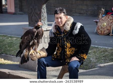 ALMATY, KAZAKHSTAN - MARCH 22, 2015: Man in national Kazakh costume holding falcon big bird with eyes closed by hat at Nauryz celebration - stock photo