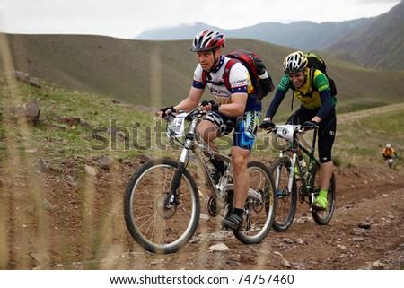 "ALMATY, KAZAKHSTAN - MAY 2: I.Baranov (N19) in action at Adventure mountain bike cross-country marathon in mountains ""Jeyran Trophy 2010"" on May 2, 2010 in Almaty, Kazakhstan. - stock photo"