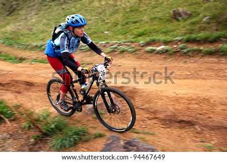 """ALMATY, KAZAKHSTAN - MAY 2: J.Grebeneva (N26) and others in action at Adventure mountain bike cross-country marathon in mountains """"Jeyran Trophy 2010"""" May 2, 2010 in Almaty, Kazakhstan. - stock photo"""
