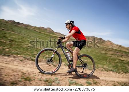 "ALMATY, KAZAKHSTAN - MAY 1, 2015: M.Getmanchuk (N26) in action at Adventure mountain bike marathon ""Jeyran Trophy 2015"" - stock photo"