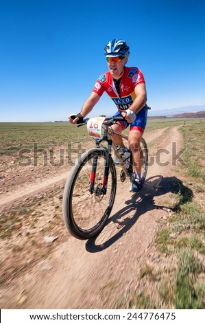 "ALMATY, KAZAKHSTAN - MAY 05, 2013: R.Nurjanov (N16) in action at Adventure mountain bike cross-country competition in mountains ""Jeyran Trophy 2013""  - stock photo"