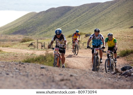 """ALMATY, KAZAKHSTAN - MAY 01: V.Vasilyev (N19) and other in action at Adventure mountain bike cross-country marathon in mountains """"Jeyran Trophy 2011"""" May 1, 2011 in Almaty, Kazakhstan. - stock photo"""