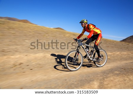 "ALMATY, KAZAKHSTAN - SEP 06, 2015: A.Ledyaev (N9) in action at Adventure mountain bike cross-country competition in mountains ""Bartogay Marathon 2015""  - stock photo"