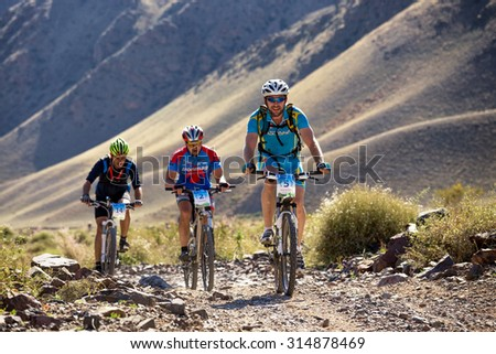 "ALMATY, KAZAKHSTAN - SEP 06, 2015: V.Vinokurov (N5) and others in action at Adventure mountain bike cross-country competition in mountains ""Bartogay Marathon 2015""  - stock photo"