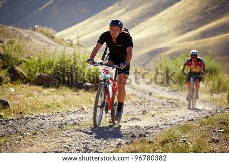 "ALMATY, KAZAKHSTAN - SEPTEMBER 05: A.Hlopotenko (N20) in action at Adventure mountain bike cross-country marathon ""Marathon Bartogay-Assy-Batan 2010"" on September 05, 2010 in Almaty, Kazakhstan. - stock photo"