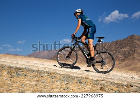 "ALMATY, KAZAKHSTAN - SEPTEMBER 09, 2014: A.Mikhailov (N27) in action at Adventure mountain bike cross-country marathon ""Marathon Bartogay-Assy-Batan""  - stock photo"