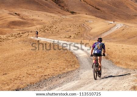 "ALMATY, KAZAKHSTAN - SEPTEMBER 09: An unidentified in action at Adventure mountain bike cross-country marathon ""Marathon Bartogay-Assy-Batan 2012"" on September 09, 2012 in Almaty, Kazakhstan. - stock photo"