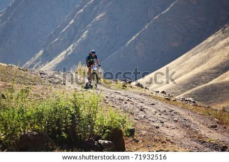 "ALMATY, KAZAKHSTAN - SEPTEMBER 05: An unidentified in action at Adventure mountain bike cross-country marathon ""Marathon Bartogay-Assy-Batan 2010"" on September 05, 2010 in Almaty, Kazakhstan. - stock photo"