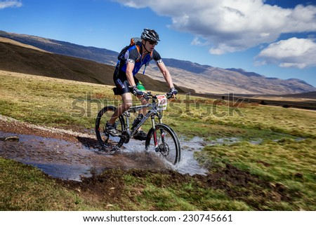 "ALMATY, KAZAKHSTAN - SEPTEMBER 09, 2014: I.Baranov (N26) in action at Adventure mountain bike cross-country marathon ""Marathon Bartogay-Assy-Batan ""  - stock photo"