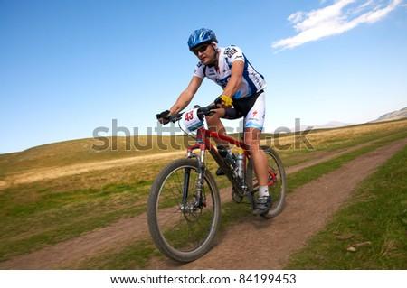 "ALMATY, KAZAKHSTAN - SEPTEMBER 04:I.Ivasenko (N43) in action at Adventure mountain bike cross-country marathon in mountains ""Marathon Bartogay-Assy-Batan 2011"" September 04, 2011 in Almaty, Kazakhstan - stock photo"
