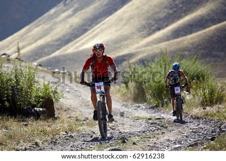 "ALMATY, KAZAKHSTAN - SEPTEMBER 05: Vasiliy Ganga (N46) in action at Adventure mountain bike cross-country marathon ""Marathon Bartogay-Assy-Batan 2010"" on September 05, 2010 in Almaty, Kazakhstan. - stock photo"
