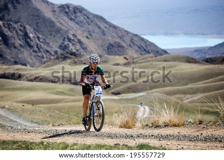 "ALMATY, KAZAKSTAN - MAY 03, 2014: A.Pak (N7) in action at Adventure mountain bike cross-country marathon in mountains ""Jeyran Trophy 2014""  - stock photo"