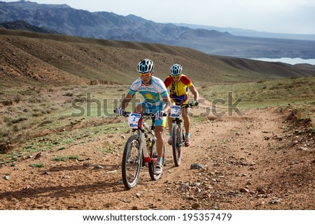 "ALMATY, KAZAKSTAN - MAY 02, 2014: K.Kazantchev (N1) in action at Adventure mountain bike cross-country marathon in mountains ""Jeyran Trophy 2014""  - stock photo"
